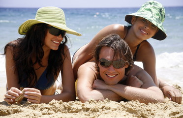 One man and two women on the beach