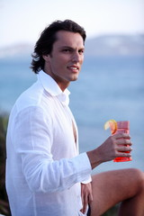 Young man holding a cocktail
