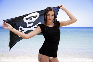 Young woman on beach holding up skull and bones flag