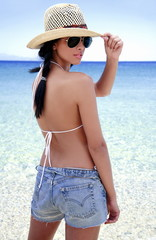 Young woman in hat and jean shorts on beach