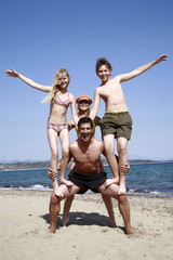 Parents with children doing pyramid on beach