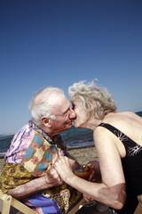 Senior couple with on beach kissing
