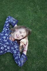 Girl on grass listening to seashell