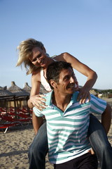 Mature adult couple piggyback on beach