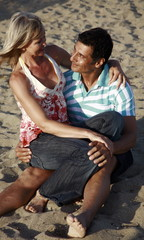 Mature adult couple sitting on beach