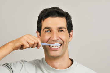 Young male adult brushing teeth