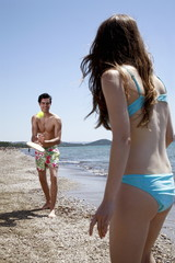 Young adult couple playing racquet ball on beach