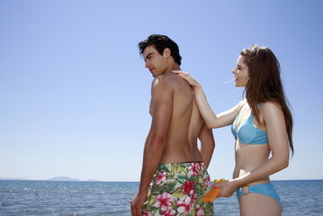 Female young adult applying suntan lotion on male's back