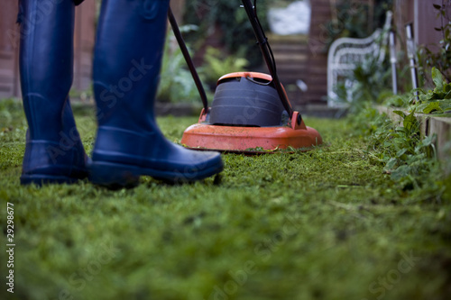 A man cutting the grass with a lawnmower