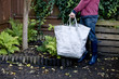 A man holding a recycling bag for garden waste