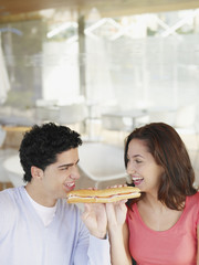 Young couple sharing a deli sandwich