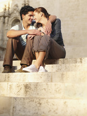 Young couple sitting outdoors on steps in front of old church