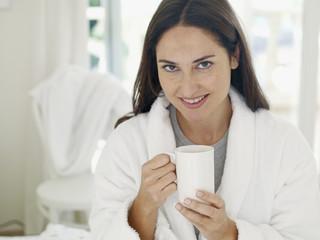 Woman in bathrobe with mug smiling