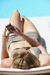 Rear view of woman sunbathing on folding chair with blackberry