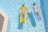 Two women on flotation devices in pool