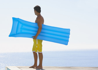 Man in swimsuit on deck by water with flotation device