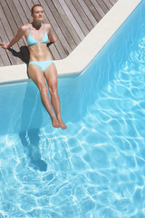 Woman in bikini sitting on pool deck sunbathing