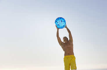 Man in swimsuit with beach ball outdoors