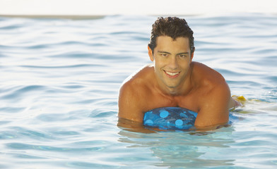 Man in pool with beach ball smiling