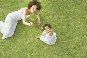 Mother and daughter on grass in summer from above