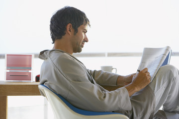 Man doing crossword puzzle in robe