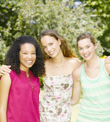 Teenage girls outdoors smiling and hugging