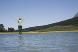 Woman standing on water with arms up