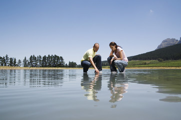 Man and woman crouching on water and pointing