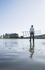 Man standing on water with ladder