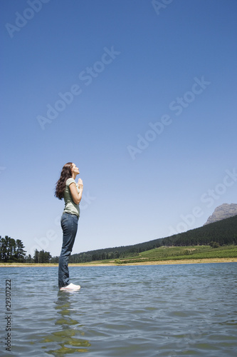 Profile of woman standing on water praying
