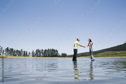 Man and woman standing on water shaking hands