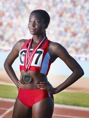 Athlete standing proudly with three medals around neck