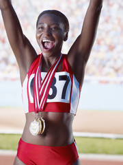 Athlete cheering with three medals around neck