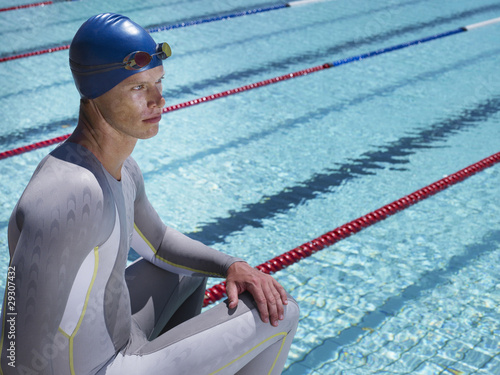 Swimmer sitting by pool