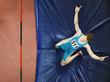 Athlete on a crash mat after high jumping