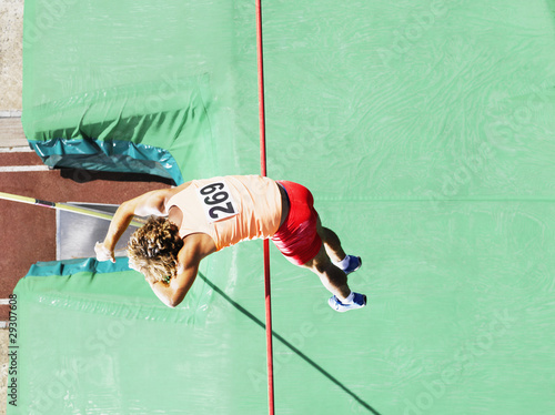 Athlete doing pole vault over a large mat