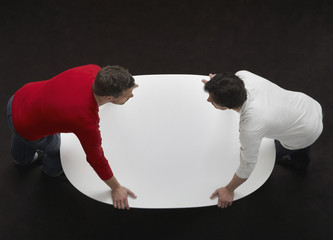 Two men leaning over a table