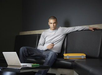 Businessman sitting with his mobile phone and laptop