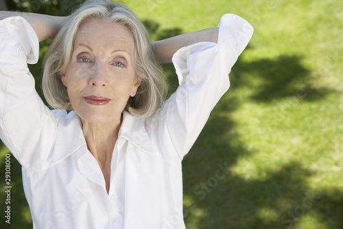Woman relaxing with hands on neck outdoors