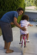 Father teaching daughter to ride bicycle in driveway