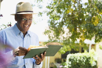 Man reading a book outdoors smiling
