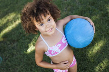 Girl in swimwear holding ball in yard