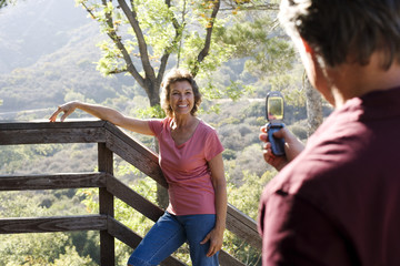 Man taking picture with camera phone of woman on staircase outdoors