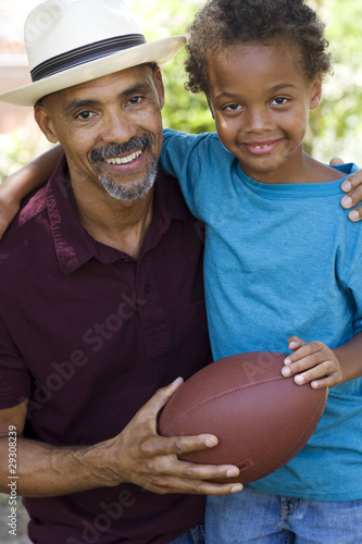 Man and young boy holding a football outdoors