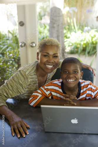 Woman and young boy at a table with laptop smiling