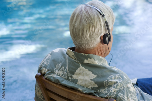 Man wearing headphones sitting by a pool
