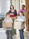 Couple with young boy and girl carrying boxes into home