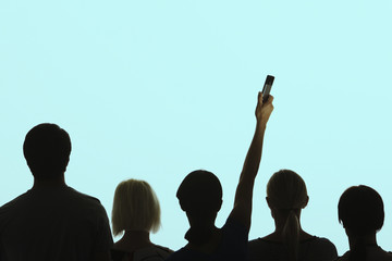 Five people standing together with one holding up her mobile phone