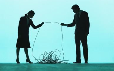 Two businesspeople holding ends of a cable and putting them together