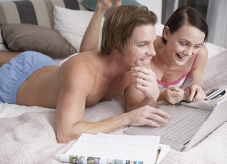 Couple in bed with a laptop and credit card